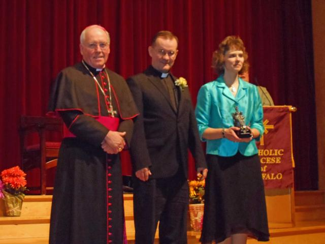 Father Matt Nycz accepts the Venerable Nelson Baker award from Bishop Malone & Kathryn Goller.